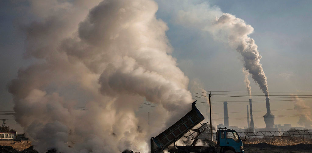 """INNER MONGOLIA, CHINA - NOVEMBER 03: A Chinese labourer unloads waste coal and stone as smoke and steam rises next to an unauthorized steel factory on November 3, 2016 in Inner Mongolia, China. To meet China's targets to slash emissions of carbon dioxide, authorities are pushing to shut down privately owned steel, coal, and other high-polluting factories scattered across rural areas. In many cases, factory owners say they pay informal """"fines"""" to local inspectors and then re-open. The enforcement comes as the future of U.S. support for the 2015 Paris Agreement is in question, leaving China poised as an unlikely leader in the international effort against climate change. U.S. president-elect Donald Trump has sent mixed signals about whether he will withdraw the U.S. from commitments to curb greenhouse gases that, according to scientists, are causing the earth's temperature to rise. Trump once declared that the concept of global warming was """"created"""" by China in order to hurt U.S. manufacturing. China's leadership has stated that any change in U.S. climate policy will not affect its commitment to implement the climate action plan. While the world's biggest polluter, China is also a global leader in establishing renewable energy sources such as wind and solar power. (Photo by Kevin Frayer/Getty Images)"""